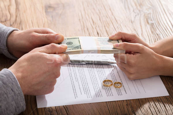 Couple's Hand Holding Currency Over The Divorce Agreement Stock photo © AndreyPopov