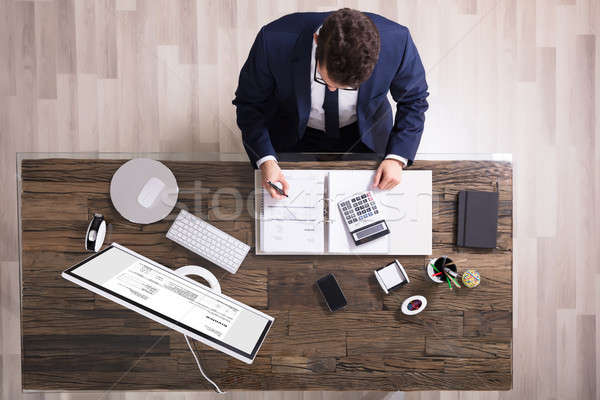 Young Businessman Calculating Invoice Stock photo © AndreyPopov