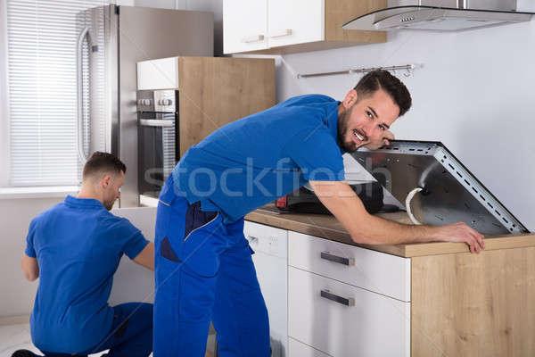 Due uomini stufa sink pipe cucina Foto d'archivio © AndreyPopov