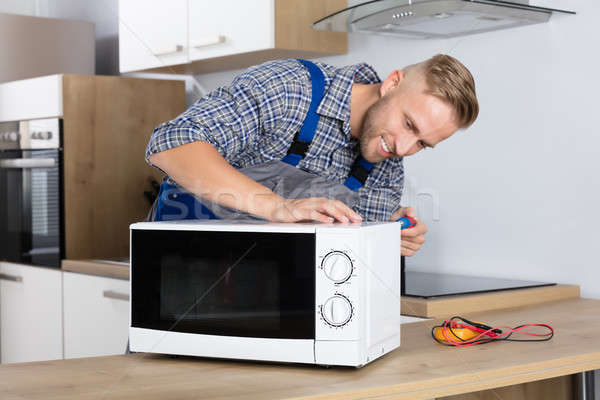 Male Serviceman Using Screwdriver To Repair Microwave Stock photo © AndreyPopov
