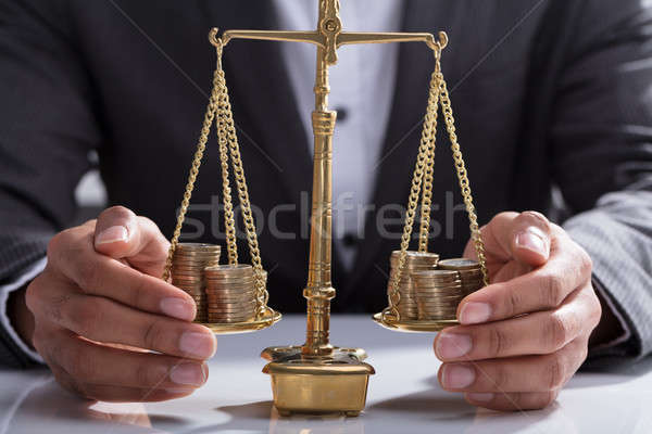 Businessperson Covering Stacked Coins On Weighing Scale Stock photo © AndreyPopov