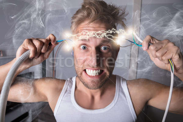 Man Holding Bared Wires Stock photo © AndreyPopov