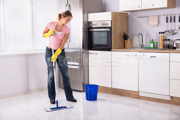 Young Woman Cleaning Kitchen Floor With Mop Stock photo © AndreyPopov