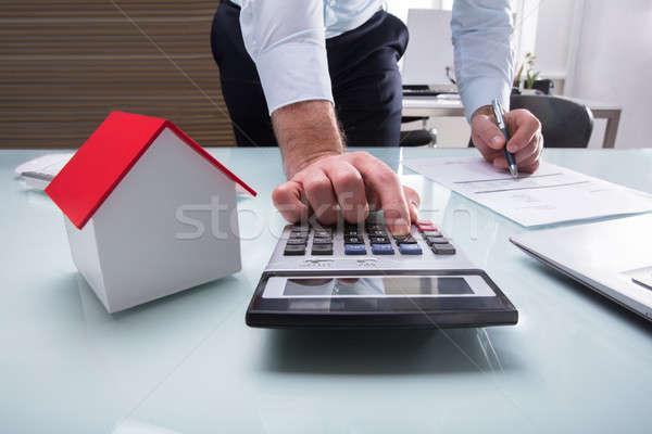 Menselijke hand Bill calculator huis model bureau Stockfoto © AndreyPopov