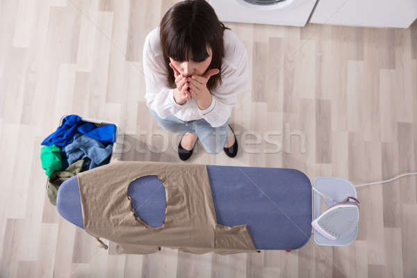 Woman Standing By Ironing Board With Burned Cloth Stock photo © AndreyPopov