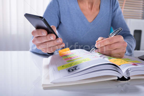 Woman Using Mobile Phone With Diary Stock photo © AndreyPopov