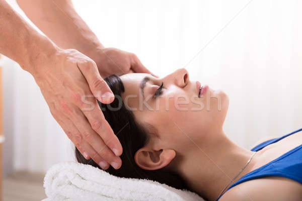 Therapist Performing Reiki Healing Treatment On Woman Stock photo © AndreyPopov