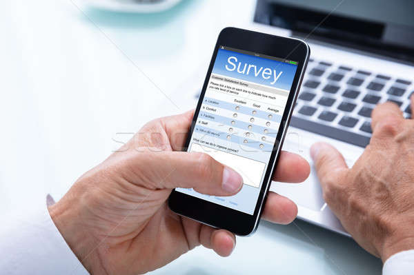 Businessman Filling Online Survey Form On Smartphone Stock photo © AndreyPopov