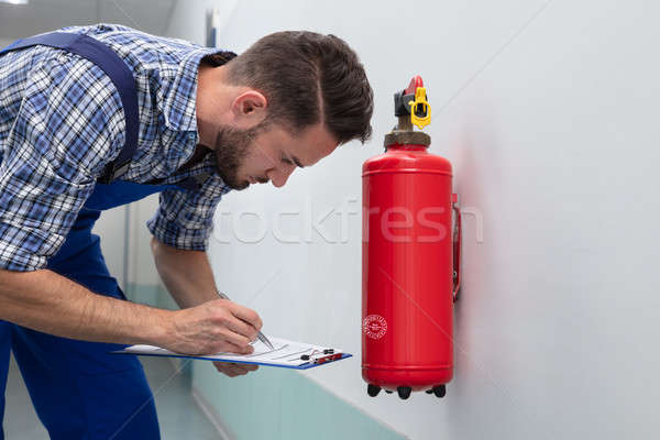 Man Checking Symbol On Fire Extinguisher Stock photo © AndreyPopov