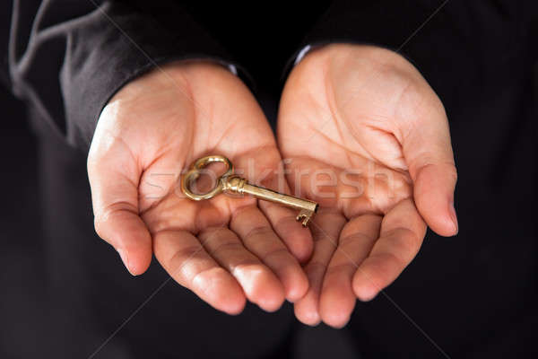 Brass key in cupped male hands Stock photo © AndreyPopov