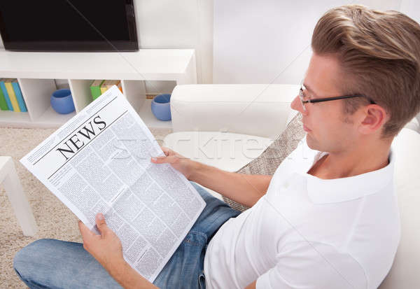 Stock photo: Young Man Reading Newspaper Sitting On Couch