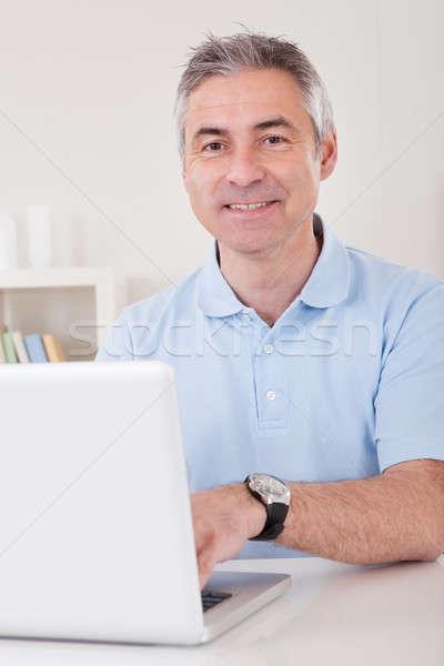 Feliz homem maduro trabalhando laptop casa papel Foto stock © AndreyPopov