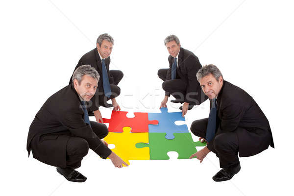 Senior business people assembling a jigsaw puzzle Stock photo © AndreyPopov