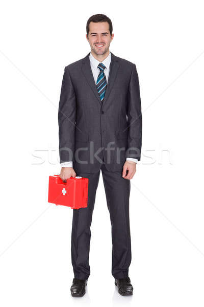 Happy Businessman Holding First Aid Box Stock photo © AndreyPopov