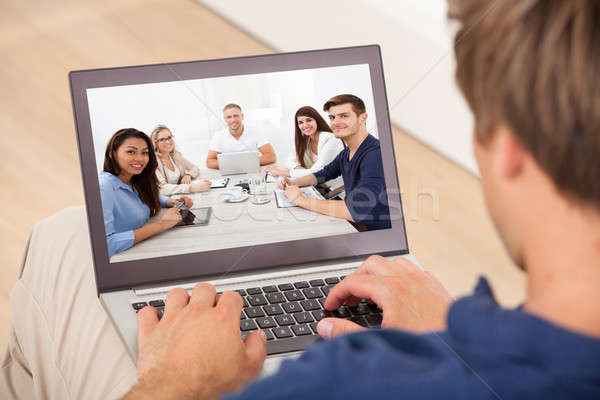 Man Attending Conference Meeting On Laptop At Home Stock photo © AndreyPopov
