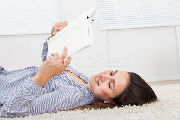 Woman Reading Book While Lying On Rug At Home Stock photo © AndreyPopov