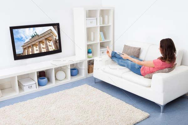 Nő tv nézés portré mosolygó nő ül kanapé Stock fotó © AndreyPopov