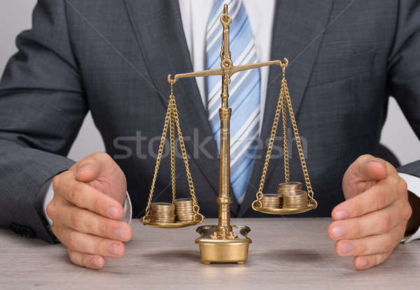 Businessman Protecting Justice Scale With Coins Stock photo © AndreyPopov