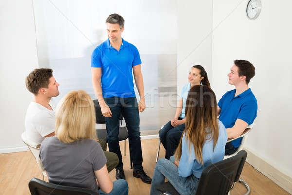 Férfi magyaráz barátok csoportkép néz nő Stock fotó © AndreyPopov