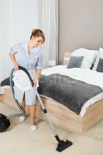 Vrouwelijke huishoudster stofzuiger gelukkig schoonmaken vloer Stockfoto © AndreyPopov
