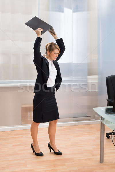 Businesswoman In Rage Throwing Laptop Stock photo © AndreyPopov