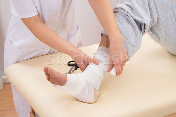 Woman Tying Bandage On Patient's Foot Stock photo © AndreyPopov