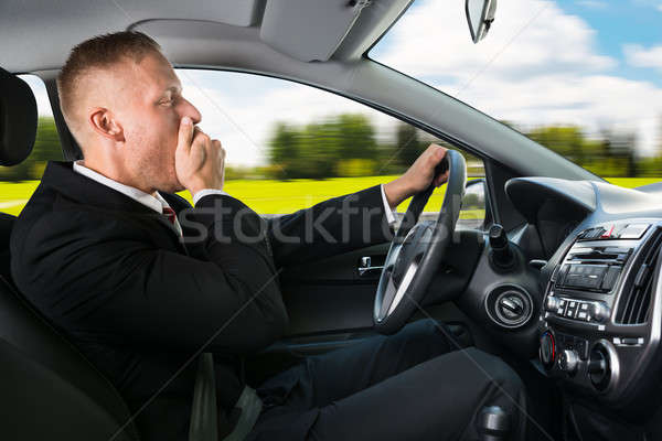 Businessman Yawning While Driving Car Stock photo © AndreyPopov
