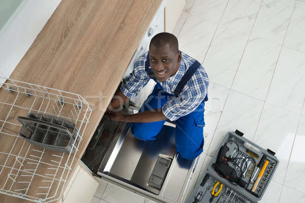 African Repairman Repairing Dishwasher Stock photo © AndreyPopov
