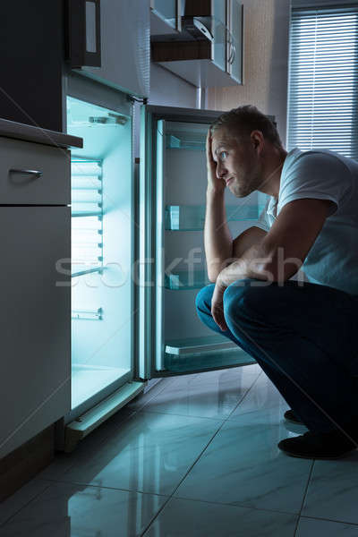 Man Looking For Food In Fridge Stock photo © AndreyPopov