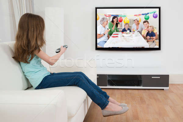 Girl With Remote Control In Front Of Television Stock photo © AndreyPopov