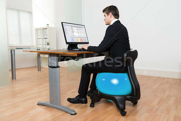 Businessman In Front Of Computer Sitting On Pilates Ball Stock photo © AndreyPopov