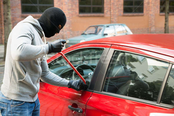 Thief With Mask Opening Car's Door By Crowbar Stock photo © AndreyPopov