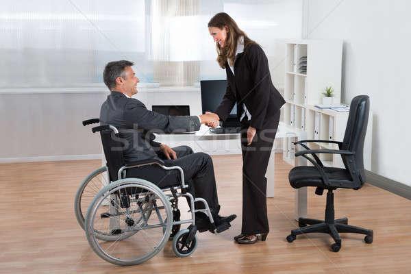 Mujer de negocios apretón de manos empresario silla de ruedas feliz oficina Foto stock © AndreyPopov