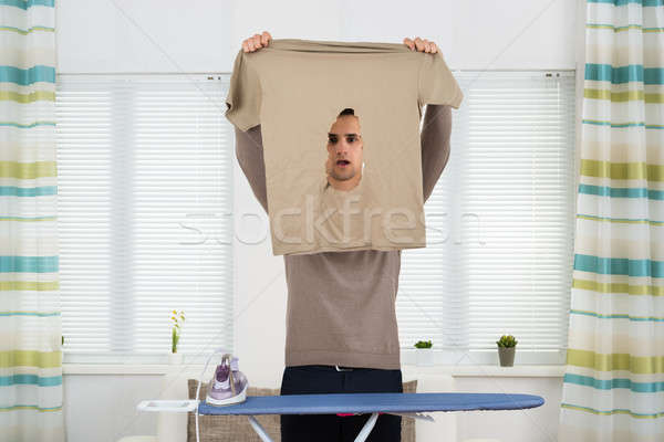 Shocked Man Looking At Iron Burnt Tshirt Stock photo © AndreyPopov