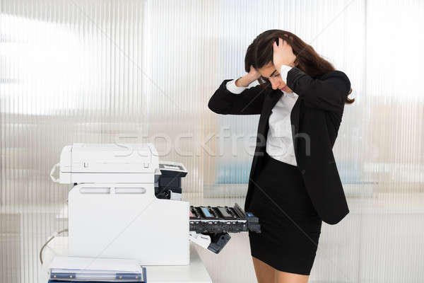 Irritated Businesswoman Looking At Printer Machine At Office Stock photo © AndreyPopov