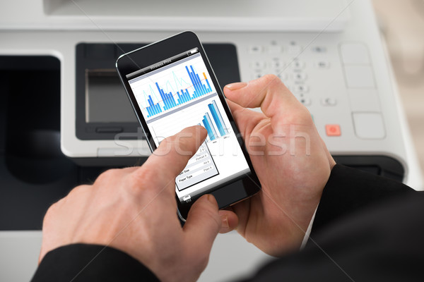 Businessman Giving Print Command On Smart Phone Stock photo © AndreyPopov