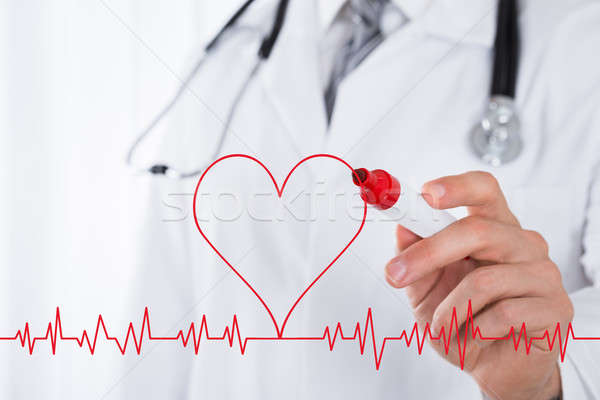 Doctor Drawing Heart Symbol Near Electrocardiogram Stock photo © AndreyPopov