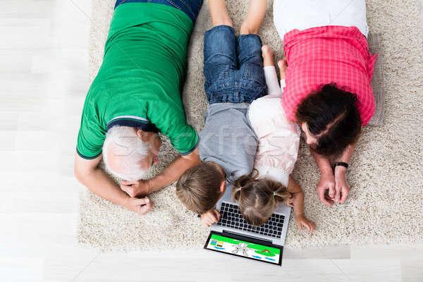 Többgenerációs család laptopot használ otthon család játszik játék Stock fotó © AndreyPopov