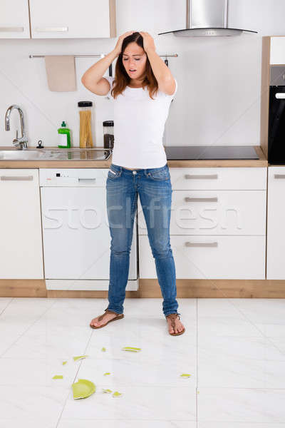 Woman Looking At Broken Plate On The Floor Stock photo © AndreyPopov