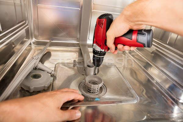 Close-up Of Repairman Fixing Dishwasher Stock photo © AndreyPopov