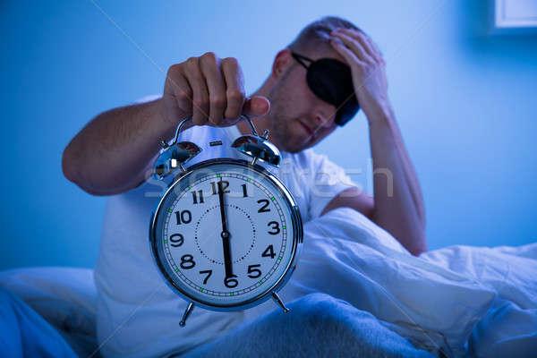 Férfi alszik ébresztőóra kéz ágy tart Stock fotó © AndreyPopov