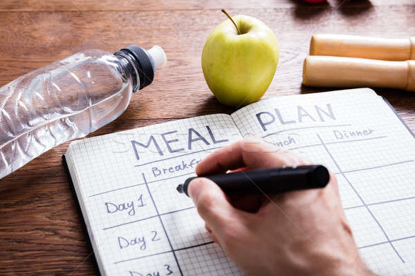 Person Hand Filling Meal Plan In Notebook Stock photo © AndreyPopov