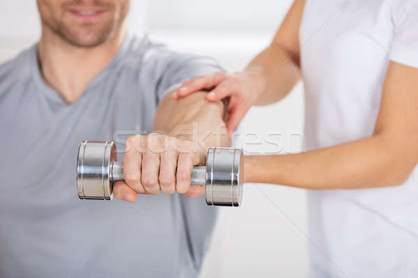 Physiotherapist Helping Man To Exercise Stock photo © AndreyPopov