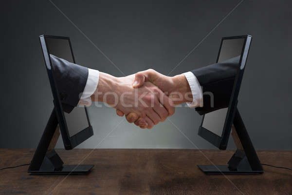 Two Men Shaking Hands Coming Out From Computer Stock photo © AndreyPopov