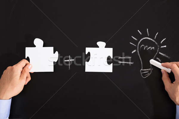 Person Drawing Idea Equation With White Puzzles Stock photo © AndreyPopov