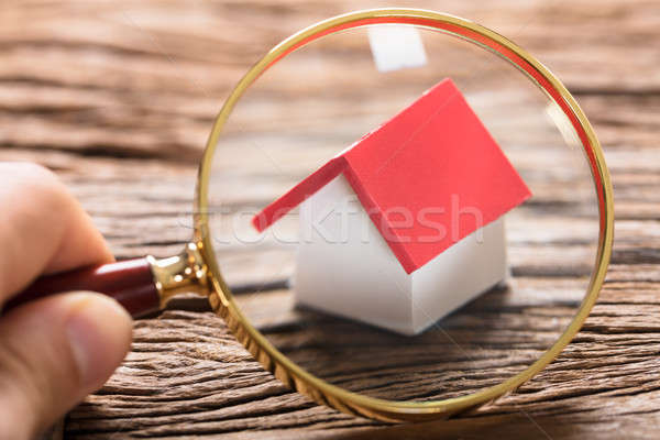 Businessman Examining Model Home With Magnifying Glass Stock photo © AndreyPopov