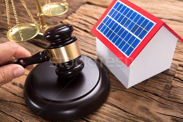 Judge's Hand Hitting Mallet By Solar Model Home On Table Stock photo © AndreyPopov