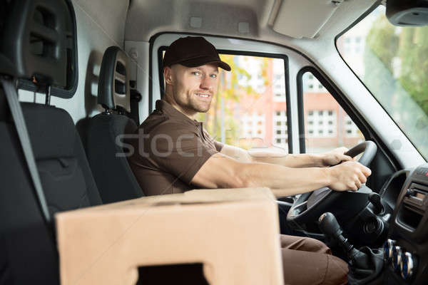Delivery Man Sitting Inside Van With Cardboard Box Stock photo © AndreyPopov