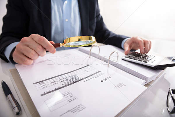 Businessperson Checking Invoice Through Magnifying Glass Stock photo © AndreyPopov