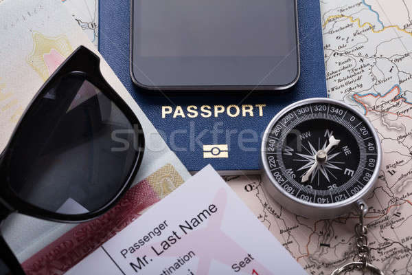Smartphone, Boarding Pass Ticket, Passport And Compass On Map Stock photo © AndreyPopov